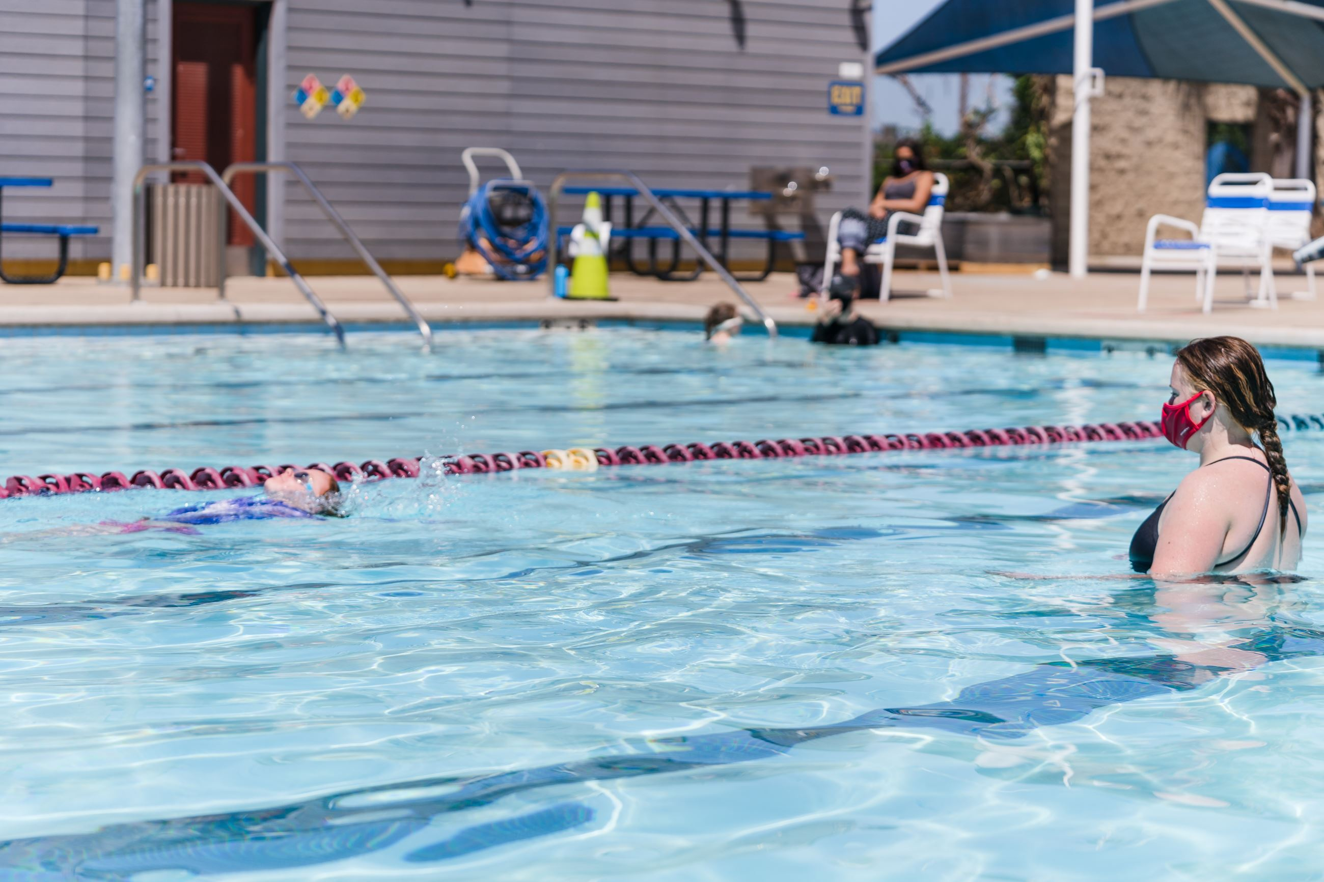 Outdoor Swim Lesson Photo, instructor wearing mask, at aquatics center